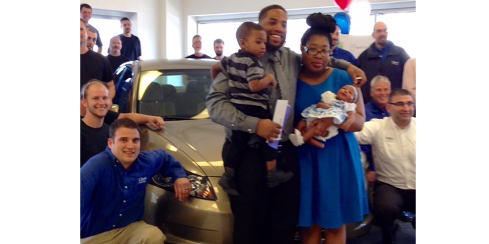 Daniel and Tynia Rosier celebrate with employees of Ciocca Collision Center, RW Mallon Auto Paint & Equipment and GEICO who teamed up to donate a refurbished 2009 Honda Accord to the family.