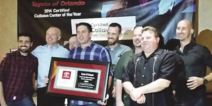 The Toyota of Orlando team accepts the Toyota Certified Collision Center Triple Crown Award.