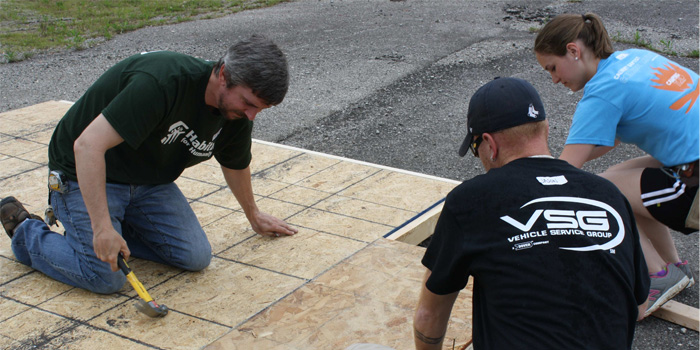 Charlie Perkins, Jason Bell and Anne Brewster were part of a VSG team that built floor decking and walls at the Habitat for Humanity ReStore before transporting them to the build site.