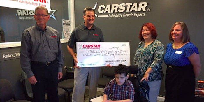 Mike Hobick, owner of CARSTAR Blue SPrings, presents a check for $5,000 to Trina Lowvell, and