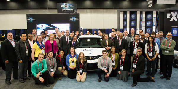 Students and faculty advisers from eight selected AutoDrive Challenge universities pose alongside a Chevrolet Bolt EV.